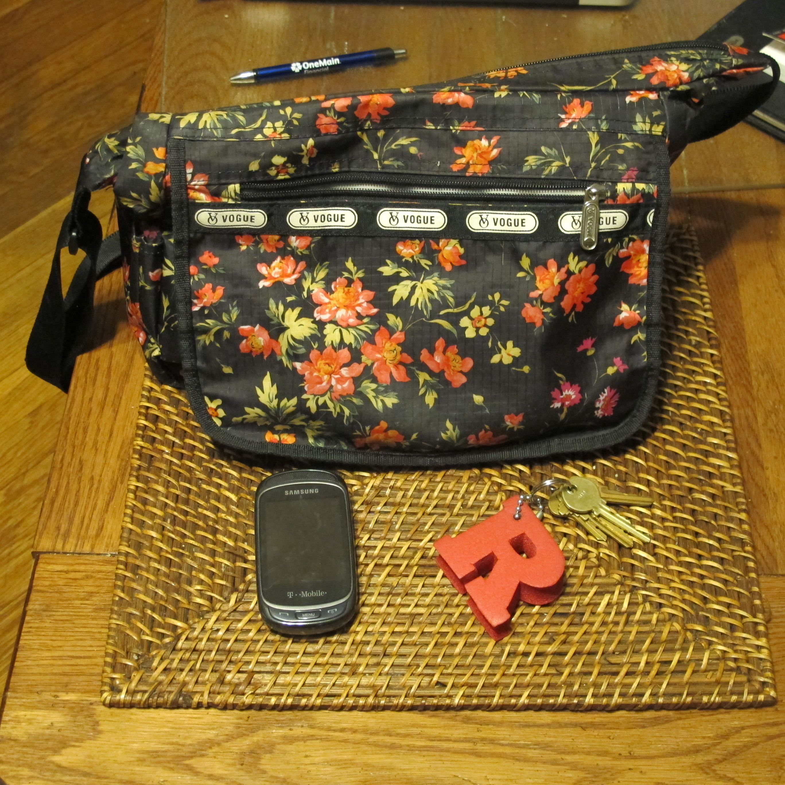 My keys, cellphone, and handbag with zippered compartment showing.